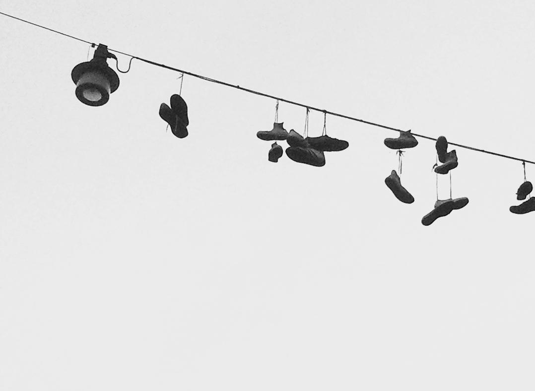 Schuhe baumeln am Kabel einer Straßenlaterne über einer Kreuzung