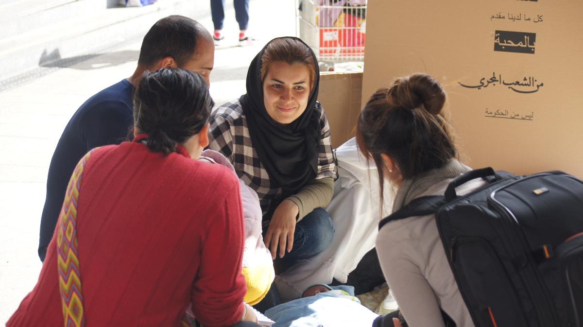Eine Familie aus Syrien hat es bis nach Budapest geschafft. Nun erklärt ihnen eine Helferin, wo es Fahrkarten für die Weiterreise gibt.